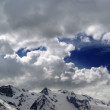 Snowy mountains in beautiful clouds — Stok fotoğraf