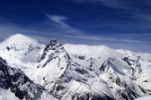 Snowy mountains and blue sky with clouds — Stok fotoğraf