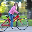 图库照片: Child riding bike in park