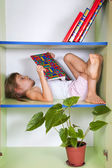 Child reading a book in a bookcase — Photo