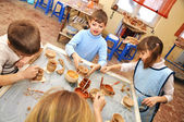 Group of children shaping clay in pottery studio — Foto Stock