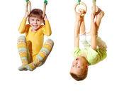 Niños jugando y haciendo ejercicio en anillos de gimnasia — Foto de Stock
