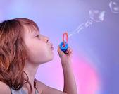 Menina, soprando bolhas de sabão em torno brilhante — Foto Stock