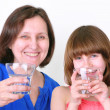 Smiling woman and girl drink water — Stock Photo