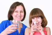 Smiling woman and girl drink water — Fotografia Stock