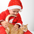Christmas toddler child plays with a cat — Stock Photo #24985877