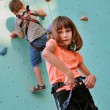 Stock Photo: Children with climbing equipment against the training wall