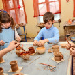 Group of children decorating their clay pottery — Stock Photo