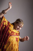Dancing little girl in traditional Indian clothing and jewelerie — Stock Photo