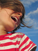 Happy laughing child against blue sky — Stok fotoğraf