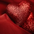 Abstract Valentine's backgrounds over red textile with tho heart — Stock Photo