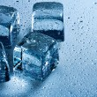 Stock Photo: Ice cube and water drops on the wet background