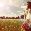 Beauty young woman walking around the summer meadow — Stock Photo #27939109