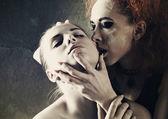 Vampire's kiss. Fantasy female portrait against dark grungy back — Stock Photo