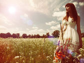 Beauty young woman walking around the summer meadow — Stock Photo