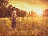 在草地上,在傍晚的阳光下的女性肖像上 — 图库照片