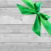 Green Christmas bow on grunge wooden grey background with space for text — Stock Photo