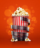 Cinema concept with paper bucket with popcorn and film tape — Stock Vector