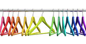 Rainbow coat hangers on clothes rail — Stok fotoğraf
