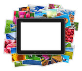 Blank tablet computer on heap of colorful photos — Stock Photo