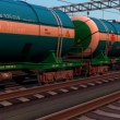 Freight train with petroleum tank cars passing by the railway station on sunset - Foto Stock
