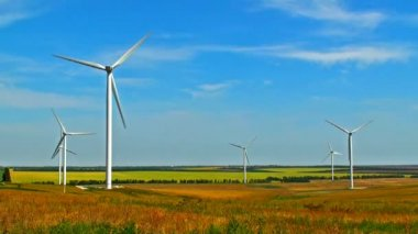 Scenic view of rotating wind turbines on field against blue sky — Stock Video
