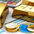 Gold ingots and coins on financial reports - Foto Stock