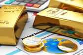 Gold ingots and coins on financial reports — Stock Photo