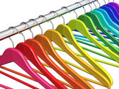 Rainbow coat hangers on clothes rail — Stock Photo