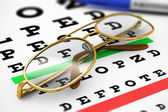 Eyeglasses and Snellen vision test — Stockfoto