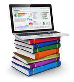 Laptop på trave färg böcker — Stockfoto
