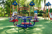 Little brother and sister spinning on roundabout — Stock Photo