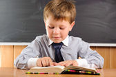 Cute boy with books at the desk — Stock Photo
