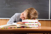 Sleeping boy with books at the desk — Stock Photo
