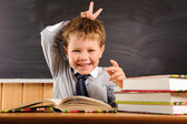 Cute boy fooling at the lesson — Stock Photo