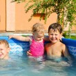 Stock Photo: Two brothers and baby sister in the pool
