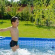 Cute boy jumping in swimming pool — Stock Photo