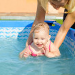Young mother helping her daughter to swim — Stock Photo #12255800