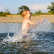 Little boy splashing water in river — Stock Photo