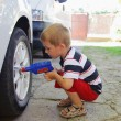 Lillte child playing in auto mechanic — Stock Photo