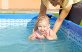 Young mother helping her daughter to swim — Stock Photo