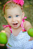 Cute little girl gives green apples — Stock Photo