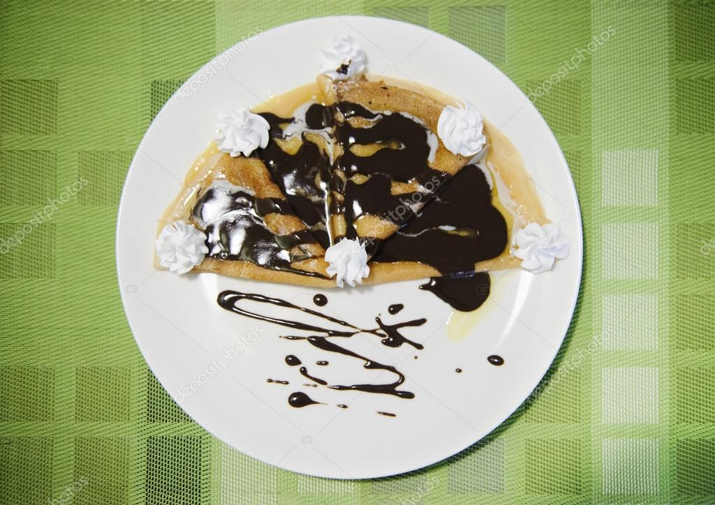 Pancakes with chocolate on white plate on green tablecloth — Stock Photo #12546902