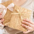 Christmas present in golden wrap — Stock Photo #13855601