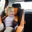 Happy child smiling in car seat — Photo