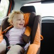 Happy child smiling in car seat - Stockfoto