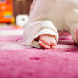 Baby crawling on pink carpet — Stock Photo #13856304