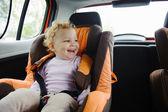 Enfant heureux souriant dans siège auto — Photo