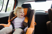 Happy child smiling in car seat — Stockfoto