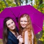 Two girls under umbrella in autumn park — Stock Photo